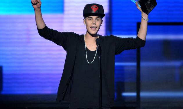 "FILE - In this Nov. 18, 2012 file photo, Justin Bieber accepts the award for favorite album - pop/rock for ""Believe"" at the 40th Anniversary American Music Awards, in Los Angeles. On Jan. 1, 2013, a paparazzo was struck by a car and killed in Los Angeles while pursuing photos of Bieber's white Ferrari. Bieber was not in the car. (Photo by John Shearer/Invision/AP, File)"