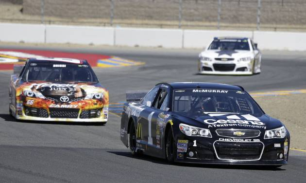 Jamie McMurray leads Tomy Drissi, left, and Dale Earnhardt Jr., top right, during qualifying for the NASCAR Sprint Cup series auto race Saturday, June 21, 2014, in Sonoma, Calif. McMurray was the pole winner. (AP Photo/Eric Risberg)