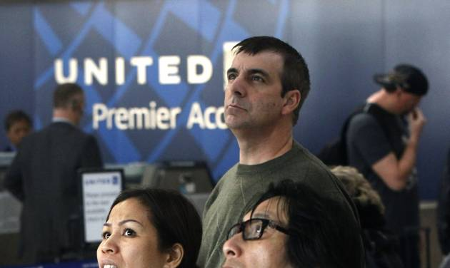 United Airlines passengers look at the flight schedule displays at Chicago's O'Hare International Airport Thursday, Nov. 15, 2012. Passengers in several cities say a massive computer outage has stranded United passengers at airports across the country, resulting in at least the third major computer outage for the Chicago-based airline since June. (AP Photo/Charles Rex Arbogast)