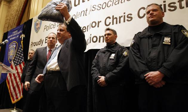 New Jersey Gov. Chris Christie holds up a fleece jacket given to him by the Port Authority of New York and New Jersey Tuesday, Jan. 22, 2013, in Elizabeth, N.J., to replace the one that he famously wore for days after Superstorm Sandy. Christie also picked up an endorsement from the union representing police at the Port Authority of New York and New Jersey, a group that backed Democrat Jon Corzine four years ago. Christie told the gathering that he will continue to support Port Authority police in their dispute with the New York City police department over who will provide security at the former World Trade Center site. (AP Photo/Mel Evans)