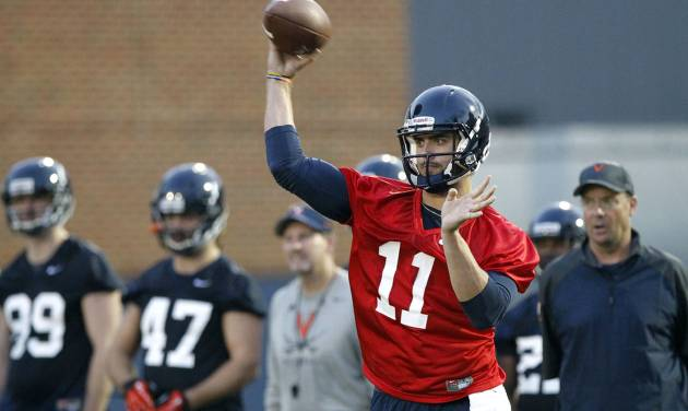Virginia quarterback Greyson Lambert (11) throws a pass during the first fall football practice on Monday, Aug. 25, 2014 in Charlottesville, Va.   The redshirt sophomore quarterback is preparing for the first start of his college career on Saturday against No. 7 UCLA.    (AP Photo/The Daily Progress, Ryan M. Kelly)