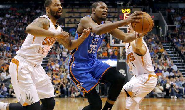 Oklahoma City Thunder forward Kevin Durant (35) drives between Phoenix Suns guard Goran Dragic, right, of Slovenia, and Markieff Morris during the first half of an NBA basketball game on Sunday, April 6, 2014,in Phoenix. (AP Photo/Matt York)