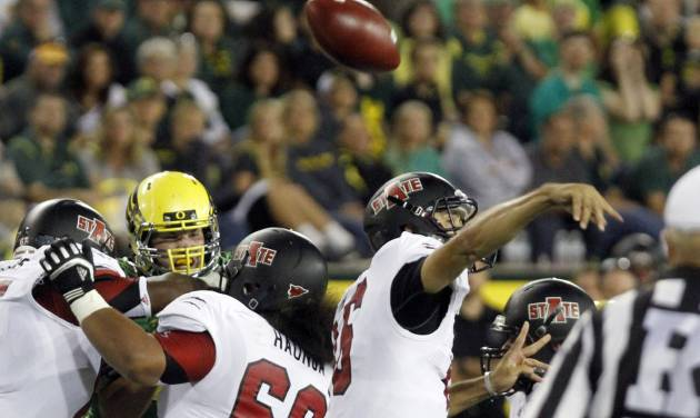 Arkansas State quarterback Ryan Aplin loses his grip on the ball while passing during the first half of their NCAA college football game against Oregon in Eugene, Ore., Saturday, Sept. 1, 2012. Aplin recovered his fumble on this play.(AP Photo/Don Ryan)