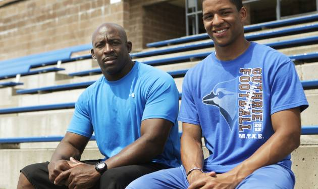 Kai Callins, 17 of Guthrie (right), poses for a photo at Jelsma Stadium in Guthrie with his father Reggie Callins (left.) Kai Callins is recovering from a torn ACL last season, and his father has been his trainer throughout the recovery process. Photo by KT KING, The Oklahoman  KT King - KT KING