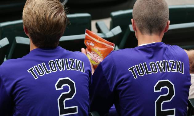 Fans wear shirts emblazoned with the misspelled surname of Colorado Rockies All-Star shortstop Troy Tulowitzki that were given away to attendees as the Rockies hosted the Pittsburgh Pirates in a baseball game in Denver, Saturday, July 26, 2014. (AP Photo/David Zalubowski)