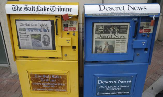 The Salt Lake Tribune and Deseret News,  newspaper boxes are shown next to each other  Monday, June 16, 2014, in Salt Lake City. A group of former employees of The Salt Lake Tribune have filed a lawsuit to suspend the newspaper's joint operating agreement with the Deseret News, arguing that the terms violate federal antitrust laws and undermine the Tribune's independent voice.   (AP Photo/Rick Bowmer)