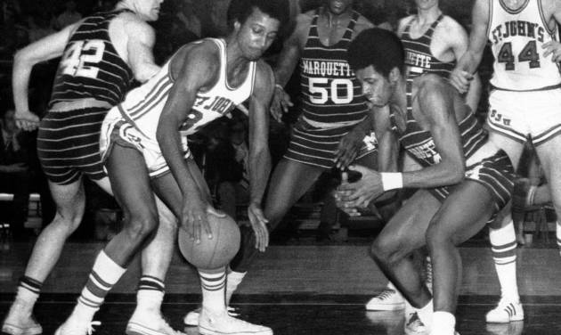 FILE - In this March 21, 1970, file photo, Marquette's Dean Meminger, right, attempts to take the ball from St. John's Richard Gilkes, front left, during a National Invitational Tournament basketball game at New York's Madison Square Garden. Meminger, who played a reserve role on the New York Knicks' 1973 NBA championship team, was found dead Friday, Aug. 23, 2013, in a New York hotel room. He was 65. (AP Photo/Marty Lederhandler, File)