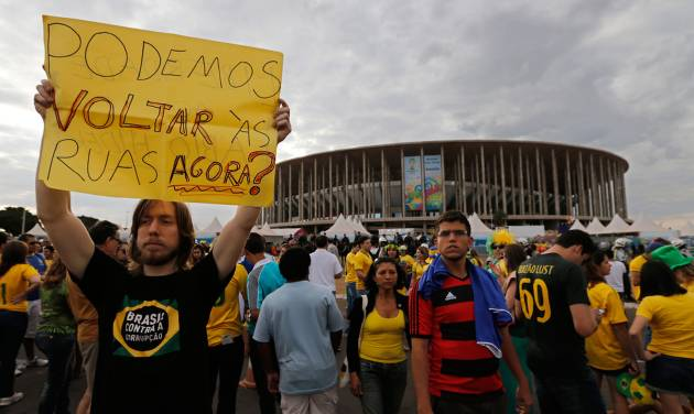 """A demonstrator shows poster written in Portuguese that reads, """"Can we go back to the streets now?"""" during the third place finish World Cup match between Brazil and the Netherlands, outside the National Stadium in Brasilia, Brazil, Saturday, July 12, 2014. Robin van Persie and Daley Blind scored early goals to help give the Netherlands a 3-0 win over host Brazil in the third-place match at the World Cup. (AP Photo/Eraldo Peres)"""