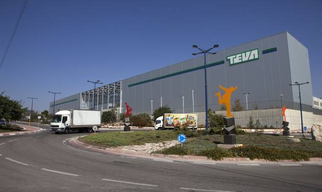 Trucks run past Teva Pharmaceutical Logistic Center in the town of Shoam, Israel, Wednesday, Oct. 16, 2013. As the world's leading maker of generic drugs, Teva Pharmaceutical Industries Ltd. has evolved not only into a giant in the pharmaceutical world but also a source of pride for Israel. Now, following an announcement of planned layoffs and revelations it enjoys sweeping tax exemptions, this homegrown jewel of the Israeli economy is on the defensive and fighting to save its reputation as the country's flagship company. (AP Photo/Dan Balilty)