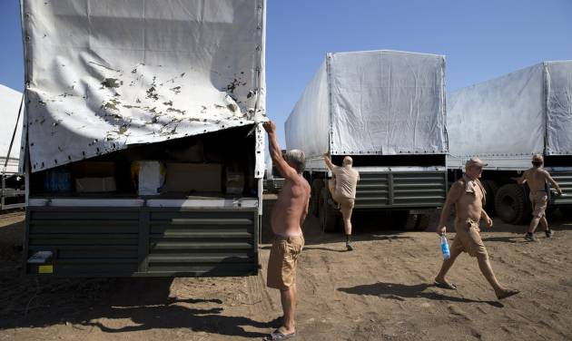 CORRECTS NAME OF TOWN TO KAMENSK-SHAKHTINSKY. Drivers prepare to show cargos to journalists in a field where the aid convoy is parked in Kamensk-Shakhtinsky, Russia, Friday, Aug. 15, 2014. The Ukrainian government threatened to use all means available to block the convoy if the Red Cross was not allowed to inspect the cargo. Such an inspection would ease concerns that Russia could use the aid shipment as cover for a military incursion in support of the separatists, who have come under growing pressure from government troops. (AP Photo/Pavel Golovkin)