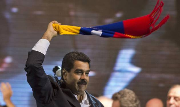 Venezuela's President Nicolas Maduro waves a scarf with the colors of the Venezuelan flag at a rally in Buenos Aires, Argentina, Wednesday, May 8, 2013. Maduro and his Argentine counterpart and ally, Cristina Fernandez, announced new energy and food agreements Wednesday, then Maduro cheered supporters of Argentina's president with a rousing speech at a soccer-stadium rally. (AP Photo/Victor R. Caivano)