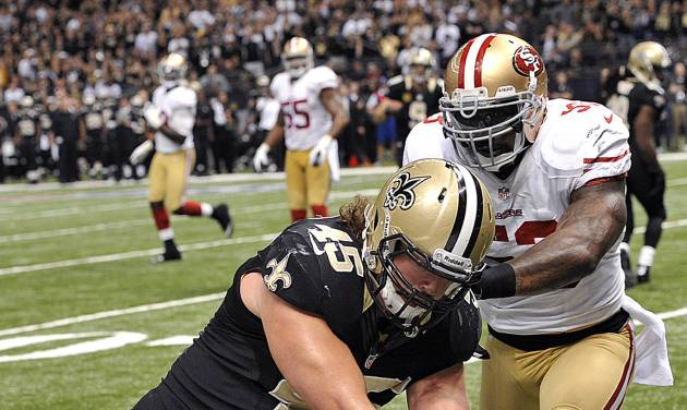 New Orleans Saints fullback Jed Collins (45) scores a touchdown as San Francisco 49ers inside linebacker NaVorro Bowman (53) covers in the second half of an NFL football game in New Orleans, Sunday, Nov. 25, 2012. (AP Photo/Bill Feig)