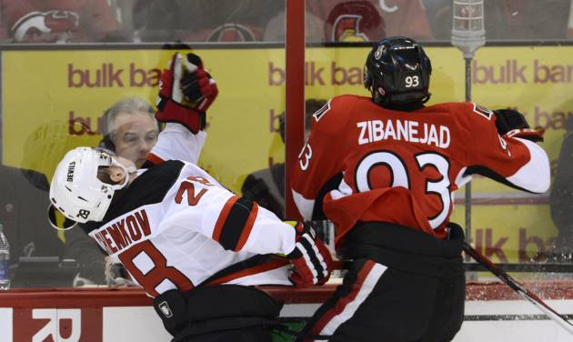 New Jersey Devils defenseman Anton Volchenkov,left,  collides with Ottawa Senators center Mika Zibanejad, right, along the boards during first period NHL action in Ottawa, on Monday March 25, 2013.  (AP Photo/The Canadian Press, Adrian Wyld)