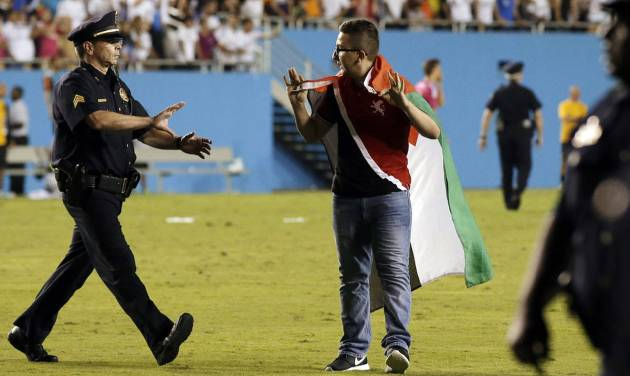 Police officers approach a fan that ran onto the field with several others during the second half of a Guinness International Champions Cup soccer tournament match between Roma and Real Madrid, Tuesday, July 29, 2014, in Dallas. Roma won 1-0. (AP Photo/Tony Gutierrez)