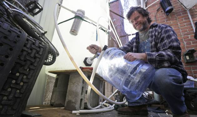 Jonathan Steele, owner of Bluegrass Kitchen, fills a jug with cleaning water in the back of his restaurant in Charleston, W.Va., Tuesday, Jan. 14, 2014. Steele installed a large tank in the back of his restaurant and was able to open his restaurant using bottled water on Sunday.  .  (AP Photo/Steve Helber)