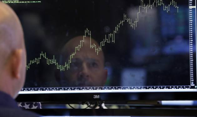 Specialist Jay Woods is reflected in a screen at his post on the floor of the New York Stock Exchange Thursday, Oct. 10, 2013. Wall Street roared in approval Thursday after Washington appeared to break an impasse that threatened to push the country into default.  (AP Photo/Richard Drew)