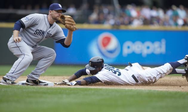 Seattle Mariners' James Jones steals third base as San Diego Padres third baseman Chase Headley attempts to make a tag during the fifth inning of a baseball game in Seattle, Tuesday, June 17, 2014. (AP Photo/Stephen Brashear)