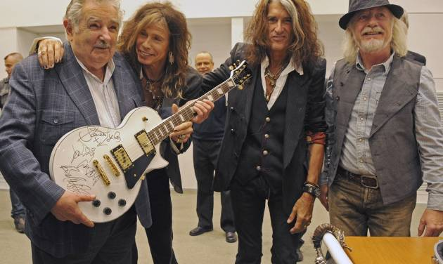 """FILE - In this Oct. 8, 2013 file photo released by Uruguay's Press Office, President Jose Mujica, left, poses with Aerosmith's band members Steven Tyler, second from left, Joe Perry, second from right, and Brad Whitford after receiving an autographed guitar as a gift at presidential house in Montevideo, Uruguay. While outside his country he is an international figure, well known for his modest lifestyle, consistent with his ideals and his good-nature, among his own people Uruguay's President known as """"Pepe"""" does not generate such devotion and many question his management. (AP Photo/Uruguay Press Office, Alvaro Salas, File)"""