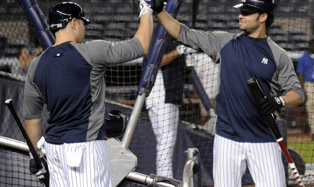 New York Yankees' Nick Swisher, right, and Russell Martin high-five during baseball practice Friday, Oct. 5, 2012, at Yankee Stadium in New York for the American League division series. (AP Photo/Bill Kostroun)