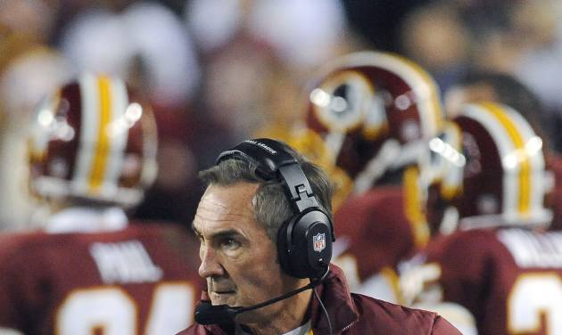 In this Sunday, Jan. 6, 2013, photo, Washington Redskins coach Mike Shanahan watches during the first half of an NFL wild card playoff football game against the Seattle Seahawks in Landover, Md. Shanahan has come under fire in the wake of Robert Griffin III reinjuring his right knee in Sunday's 24-14 wild-card loss to Seattle. The criticism has ranged from whether Shanahan cared enough for his sensational rookie to whether the natural protocol for dealing with injuries was followed. (AP Photo/Richard Lipski)