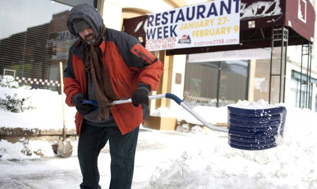 Tom Sheridan, LaSalle Grill's executive chef, shoves a path to the street from the sidewalk outside of the restaurant on Monday, Jan. 27, 2014, in downtown South Bend, Ind. Sub-freezing temperatures and blowing snow returned to the Michiana area yet again as the City of South Bend declared a winter weather emergency. (AP Photo/South Bend Tribune, James Brosher)