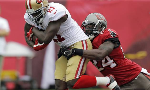 FILE - In this Dec. 15, 2013, file photo, San Francisco 49ers running back Frank Gore (21) is grabbed by Tampa Bay Buccaneers cornerback Darrelle Revis (24) during the first quarter of an NFL football game in Tampa, Fla. The Buccaneers have parted ways with Revis, and he officially agreed to terms with the New England Patriots on Thursday, March 13, 2014.  (AP Photo/Chris O'Meara, File)