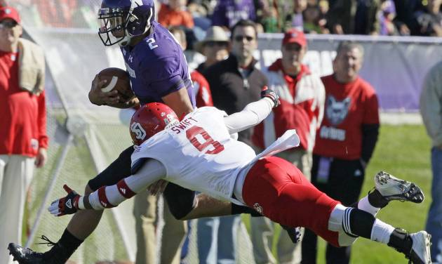 South Dakota defensive back Aaron Swift (9) tackles Northwestern quarterback Kain Colter (2) during the first half of an NCAA college football game in Evanston, Ill., Saturday, Sept. 22, 2012. (AP Photo/Nam Y. Huh)