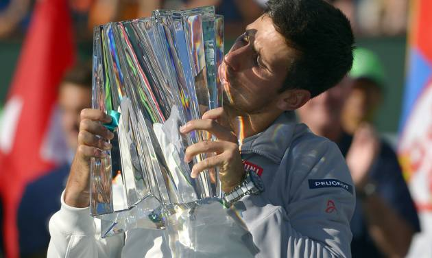 Novak Djokovic, of Serbia, kisses the trophy after he beat Roger Federer, of Switzerland, 3-6, 6-3, 7-6 to win the final match of the BNP Paribas Open tennis tournament, Sunday, March 16, 2014, in Indian Wells, Calif. (AP Photo/Mark J. Terrill)