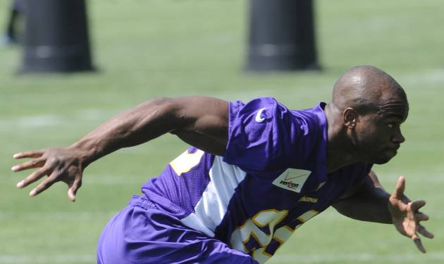 Minnesota Vikings NFL football running back Adrian Peterson, left, works out for trainer Eric Sugarman during the first day of minicamp, Tuesday, June 19, 2012, in Eden Prairie, Minn. Peterson is recovering from knee surgery for a torn ACL suffered last season. (AP Photo/Jim Mone)