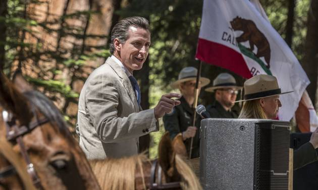 In this Monday, June 30, 2014, photo provided by Yosemite Conservancy, California Lt. Gov. Gavin Newsom addresses the public gathered at a ceremony in Yosemite National Park to marking the 150th Anniversary of the Yosemite Grant Act and groundbreaking for the restoration of the Mariposa Grove of Giant Sequoias. President Abraham Lincoln signed the Yosemite Grant on June 30, 1864, ushering in the national park idea. (AP Photo/Yosemite Conservancy, Al Golub)