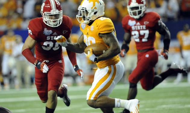 Tennessee running back Rajion Neal (20) tries to get by the defense of North Carolina State safety Brandan Bishop (30) and safety Earl Wolff (27) during the first half of the Chick-fil-A Kickoff Game, beginning the NCAA college football season, in Atlanta., on Friday, Aug. 31, 2012. (AP Photo/John Amis)