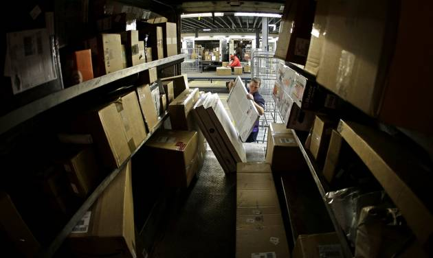 FILE - In this Monday, Dec. 16, 2013, file photo, driver Kyle Woodroof loads packages in his delivery truck in Kansas City, Mo. The Commerce Department reports on U.S. factory orders in December on Tuesday, Feb. 4, 2014. (AP Photo/Charlie Riedel, File)