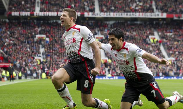 Liverpool's Steven Gerrard celebrates with teammate Luis Suarez, right, after scoring against Manchester United during their English Premier League soccer match at Old Trafford Stadium, Manchester, England, Sunday March 16, 2014. (AP Photo/Jon Super)