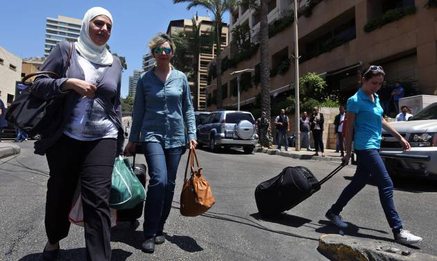 FILE - In this Thursday, June 26, 2014, file photo, tourists leave Beirut's Ramada Hotel as security forces raided some rooms in the building in Beirut. Anxiety is gripping Lebanon following a spate of suicide bombings, and an ongoing security sweep targeting militants, some of them who had been staying in four-star Beirut hotels, has triggered a wave of cancellations of hotel and flight bookings in a country already on edge. (AP Photo/Bilal Hussein, File)