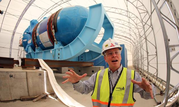 In this Friday, June 13, 2014 photo, Buzz Miller, executive vice president of nuclear development at Southern Co., stands in front of the high-pressure vessel that will be used in a new nuclear reactor at Plant Vogtle power plant in Waynesboro, Ga. Before it started building, the nuclear industry promised its new generation of plants would be constructed using giant Lego-like modules that make building faster, cheaper and produce a higher-quality result. Instead, the Louisiana factory building these modules has failed to master quality control rules, stick to schedule or replicate the approved designs, adding time and significant cost to first-of-their-kind projects. (AP Photo/John Bazemore)
