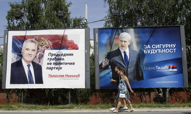 """People pass by a billboards showing presidential candidates: pro-Western former Serbian President Boris Tadic, reading: """"For save future"""", right, and Tomislav Nikolic, leader of the opposition Serbian Progressive Party (SNS), reading: """"President of all citizens, not of political party"""", in Belgrade, Serbia, Saturday, May 12, 2012. Serbian nationalists on Saturday called for nationwide street protests over alleged election fraud, fueling tensions ahead of a presidential runoff vote. Nationalist leader Tomislav Nikolic said his Serbian Progressive Party will start peaceful protests as of Sunday because """"we don't recognize"""" parliamentary and local election results held last weekend. (AP Photo/Darko Vojinovic)"""