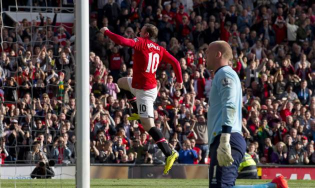Manchester United's Wayne Rooney, centre, celebrates after scoring a penalty past Norwich City's goalkeeper John Ruddy, right, during their English Premier League soccer match at Old Trafford Stadium, Manchester, England, Saturday April 26, 2014. (AP Photo/Jon Super)