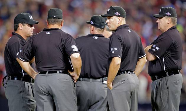 Officials stand in the center of the field as fans throw trash during the eighth inning of the National League wild card playoff baseball game between the Atlanta Braves and the St. Louis Cardinals, Friday, Oct. 5, 2012, in Atlanta. The Cardinals won baseball's first wild-card playoff, taking advantage of a disputed infield fly call that led to a protest and fans littering the field with debris to defeat the Braves 6-3. (AP Photo/Todd Kirkland)
