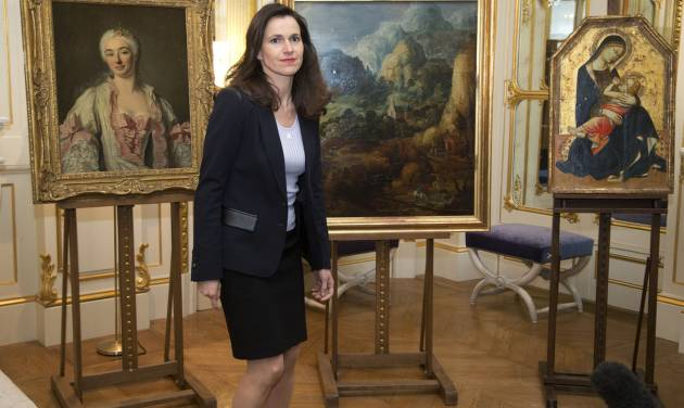 France's culture minister Aurelie Filipetti, arrives at a ceremony at the Culture Ministry in Paris, Tuesday, March 11, 2014, to return three paintings taken from their owners during World War II, background. The restitution is part of France's ongoing effort to return hundreds of looted artworks that Jewish owners lost during the war that still hang in the Louvre and other museums. (AP Photo/Michel Euler)