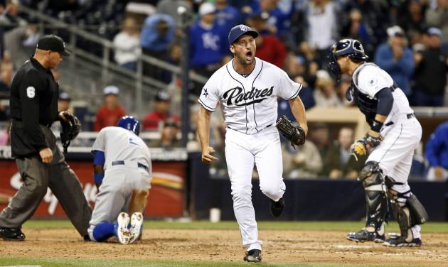 San Diego Padres relief pitcher Huston Street celebrates after Padres catcher Yasmani Grandal, right, tagged out Kansas City Royals' Alcides Escobar who was out trying to score from third on a pop out down the right field line during the ninth inning of a tied baseball game Tuesday, May 6, 2014, in San Diego. (AP Photo/Lenny Ignelzi)