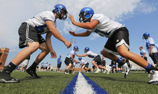 """Players run a drill during the first day of high school football practice for the Newcastle Racers in Newcastle, Okla., Monday, Aug. 12, 2013. The team is the subject of a documentary called """"The Smartest Team,"""" which examines Newcastle's efforts to reduce head injuries. It will air at 9 p.m. Wednesday on OETA. Photo by Nate Billings, The Oklahoman"""