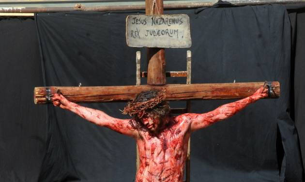 Portraying Jesus Christ a man takes part in a Way of the Cross procession, at the St. Isidoro Agricola church in Palermo, Sicily, Friday, April 18, 2014. Holy Week commemorates the last week of the earthly life of Jesus Christ culminating in his crucifixion on Good Friday and his resurrection on Easter Sunday. (AP Photo/Alessandro Fucarini)