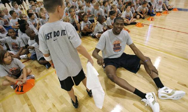 Kevin Durant hands a signed T-shirt to Noah Kern, 9 of Muskogee after a shootout during the second day of the Kevin Durant basketball camp at Heritage Hall in Oklahoma City, Thursday, June 30, 2011.  Photo by Garett Fisbeck, The Oklahoman