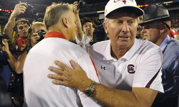 FILE - In this Sept. 10, 2011, file phot, South Carolina coach Steve Spurrier, right, and Georgia coach Mark Richt meet at midfield after the Gamecocks on 45-42 in an NCAA college football game in Athens, Ga. Coaches you'd want on the sidelines of the biggest games? South Carolina's Steve Spurrier would have to be near the top of the very short list in college football. He gets the latest chance to enhance that reputation when the sixth-ranked Gamecocks take on No. 5 Georgia on Saturday. (AP Photo/John Amis, File)