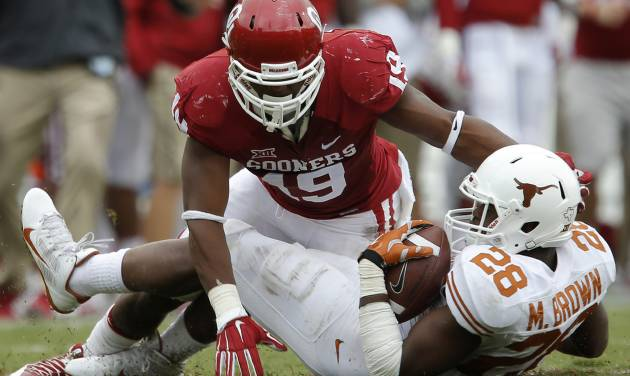 Oklahoma's Eric Striker (19) brings down Texas' Malcolm Brown (28) during the Red River Showdown college football game between the University of Oklahoma Sooners (OU) and the University of Texas Longhorns (UT) at the Cotton Bowl in Dallas on Saturday, Oct. 11, 2014. Oklahoma won 31-26. Photo by Bryan Terry, The Oklahoman