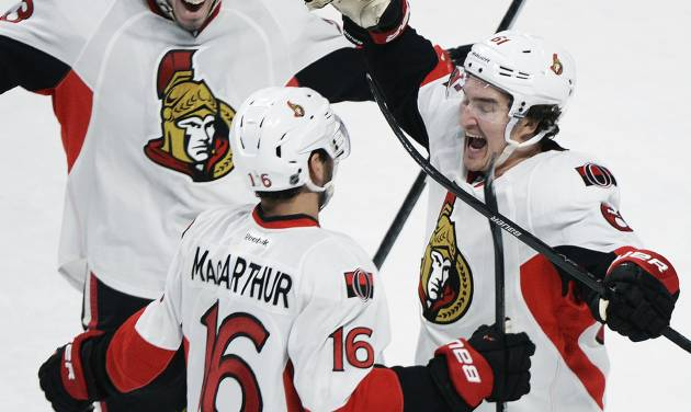 Ottawa Senators' Clarke MacArthur (16) celebrates with teammates Mika Zibanejad, left, and Mark Stone after MacArthur scored against the Montreal Canadiens during an overtime period of an NHL hockey game in Montreal, Saturday, Jan. 4, 2014. (AP Photo/The Canadian Press, Graham Hughes)