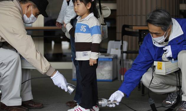 FILE - In this April 16, 2011 file photo, Wakana Nemoto, 3, standing next to her mother Naoko, receives a radiation exposure screening outside an evacuation center in Fukushima, northeastern Japan. People exposed to the highest doses of radiation during the Fukushima nuclear plant disaster in 2011 may have a slightly higher risk of cancer that is so small it probably won't even be detectable, according to a new report from the World Health Organization released on Thursday Feb. 28, 2013. (AP Photo/Hiro Komae, File)