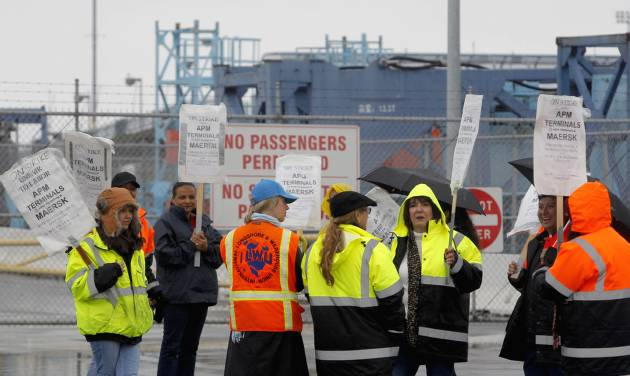 Clerical workers picket in the rain at entrance to Pier 400 at the Port of Los Angeles Thursday, Nov. 29, 2012.  Cargo ships were stacking up at the ports of Los Angeles and Long Beach as a strike by about about 70 clerical workers shut down most of the terminals that together are the nation's busiest port complex.  Dockworkers were refusing to cross the picket lines even though an arbitrator ruled the walkout invalid on Tuesday.  By Thursday morning, at least 18 ships docked and inside the adjacent harbors were not being serviced, port spokesmen said. (AP Photo/Nick Ut)