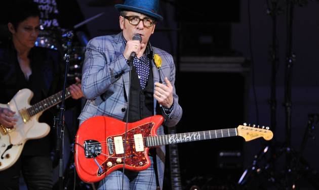 """FILE - In this March 7, 2013 file photo, musician Elvis Costello performs at """"The Music of Prince"""" tribute concert at Carnegie Hall, in New York. One of television's most successful sitcom writers is joining with Burt Bacharach and Elvis Costello to create a musical based on the artists' 1998 album """"Painted From Memory."""" Bacharach said Tuesday, May 7, 2013, that Chuck Lorre, creator of """"Two and a Half Men"""" and """"The Big Bang Theory,"""" contacted him and said he wanted to write a  story to go with the music. (Photo by Evan Agostini/Invision/AP, File)"""