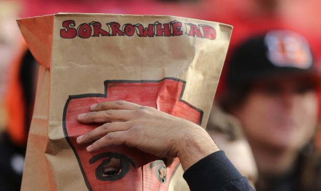 """A Kansas City Chiefs fan wears a paper bag with """"Sorrowhead"""" on it over his head as he watches the closing minutes of an NFL football game against the Cincinnati Bengals Sunday, Nov. 18, 2012, in Kansas City, MO. The Bengals won 28-6. The Chiefs have lost seven straight games. (AP Photo/Ed Zurga)"""